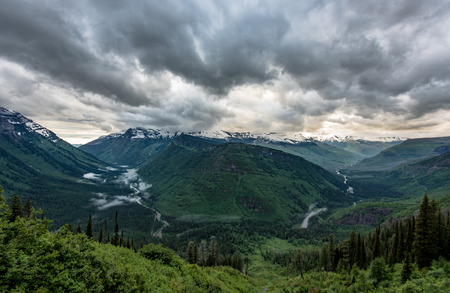 flathead: Rain Clouds Cover Snow Capped Mountain Range in summer Stock Photo