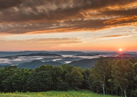 Sun setzt unter den nebeligen Bergen in Shenandoah ein Standard-Bild