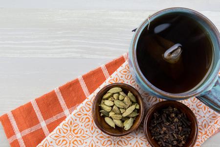 中立的な背景にオレンジのナプキンを当てに紅茶とスパイス