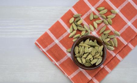 Bowl of Whole Bean Cardamom on orange plaid napkin Stock Photo
