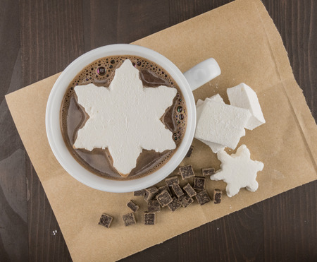 Snowflake Marshmallow in Hot Chocolate resting on brown paper