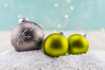 Gray Snowflake and Two Green Glass Ball Ornaments on Snow
