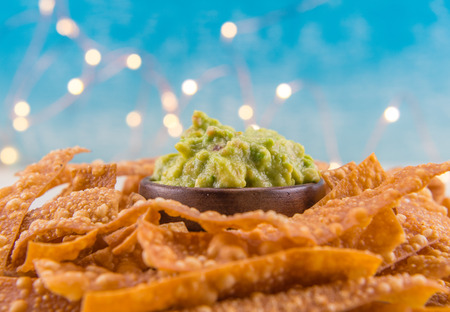 Guacamole and Chips with Lights in Background