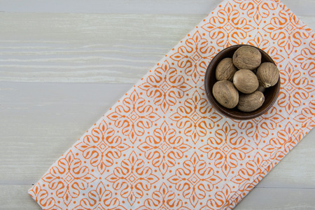 Whole Nutmeg in Bowl With Orange Napkin on wooden table