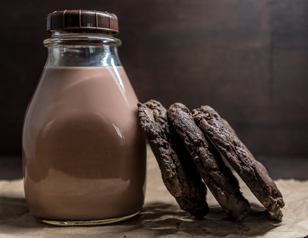 Double Chocolate Cookies Leaning Against Chocolate Milk in Vintage Bottle