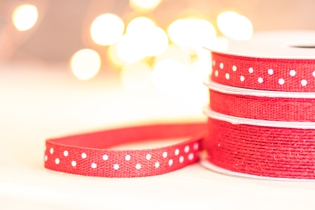 Red Ribbon with White Polka Dots in front of bright bokeh background