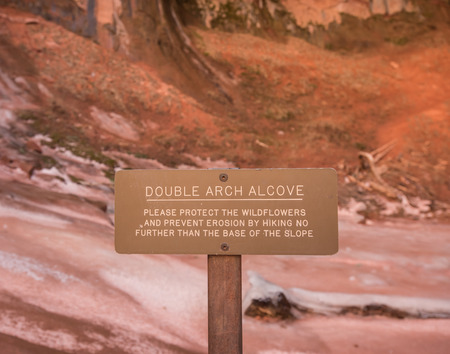cautions: Double Arch Alcove Sign cautions tourists to protect the fragile location Stock Photo