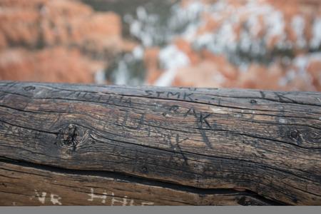 Graffiti on Worn Log Hand Rail Stock Photo