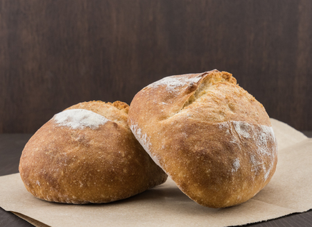 Two Dinner Rolls on Brown Paper parchment