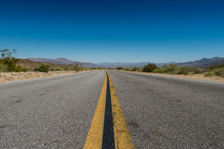 Low Angle View of Desert Road with mountains in distance