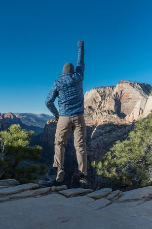 Man Jumps for Joy at Canyon Edge after a long hike