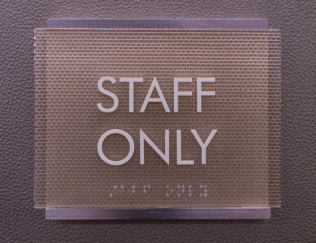 Modern Staff Only Sign with braille hangs on wall