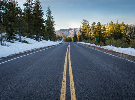 Standing in the MIddle of Snowy Mountain Road with mountains in background