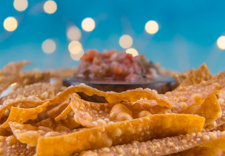 gallo: Selective Focus of Crispy Fried Bubbles on Homemade Chips with salsa in background