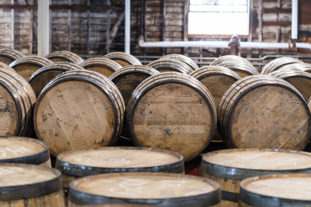 Bourbon Barrel Storage Room with barrels standing and rolling Stock Photo