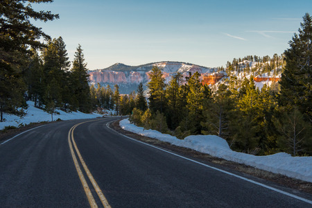 Snowy Mountain Road with Bright Orange Rocks in Background Imagens