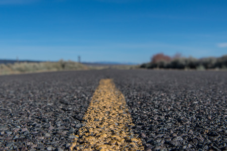 Low Angle View of Yellow Stripe on Rough Desert Road with blue sky Banco de Imagens