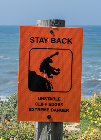 Unstable Cliffs Warning Sign on wooden post over cliff near ocean side Stock Photo