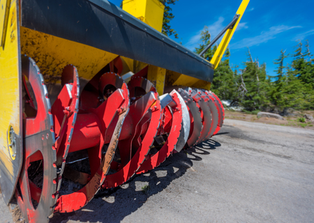 Red Blades of Snow Plow sitting idle during summer