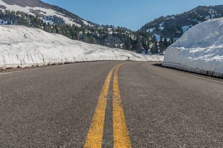 Low Angle of Road Through Snow Drifts in early summer Stock Photo
