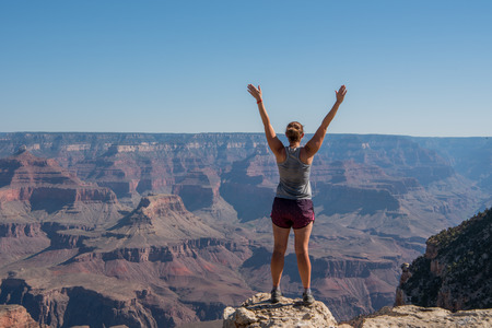 Power Posing on the Rim of the Grand Canyon on a hot summer day Stock Photo