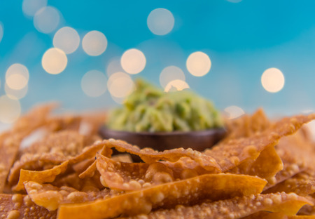 Selective Focus of Tortilla Chips with Guacamole in Background and bokeh above