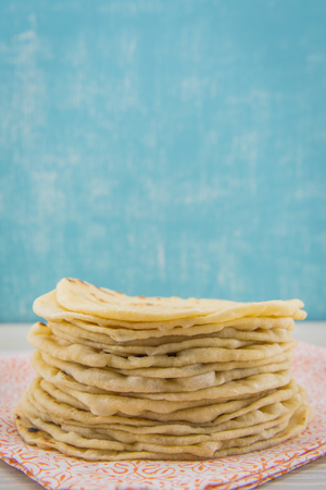 Stack of Homemade Tortillas on Orange Napkin with blue background