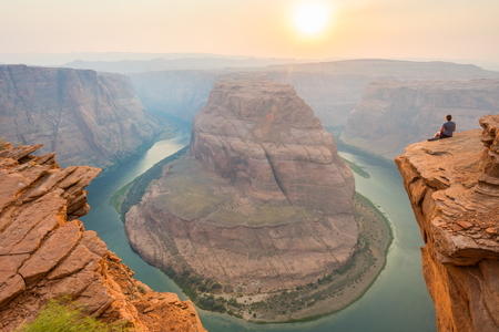 Woman Looks Out Over Horseshoe Bend on hazy afternoon