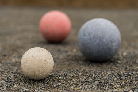 White Blue and Red Bocce Balls on gravel surface