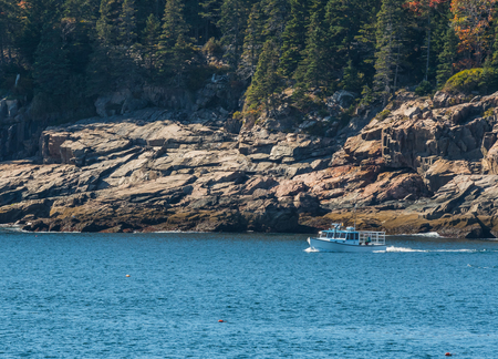 White Lobster Boat Along Rocky Maine Coast checks traps Stock Photo