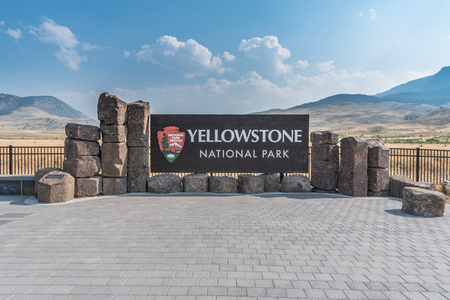 Yellowstone National Park, United States: August 5, 2017: Yellowstone National Park Sign with rollling mountains in background