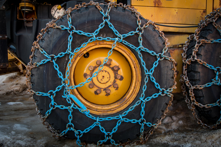 Blue Snow Chains wrapped around plow tire Stock Photo