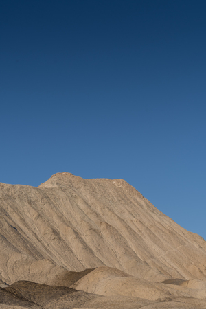 Blue Sky Over Tan Desert Hill in Death Valley wilderness