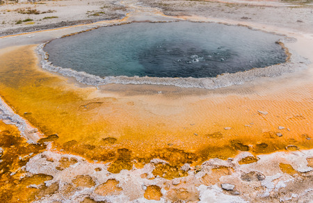 Dark Hot Spring Bubbles out on orange sulfur surface in Yellowstone
