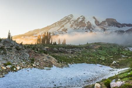 Afternoon Sun Glows Over Fog Below Mount Rainier along the skyline trail