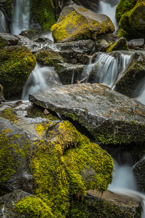 Close Up of Water Rushing Over Mossy Rocks