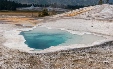 Aqua Hot Spring in Yellowstone over landscape of rolling hills Reklamní fotografie