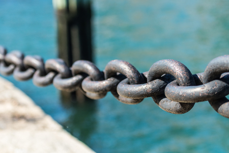 Paint Chips off Large Iron Chain Links over bright blue water