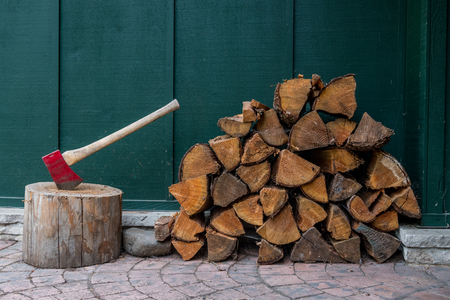 Red Axe and Pile of Fire Wood in front of dark green wall