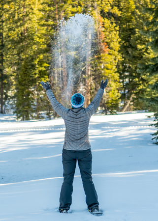 Snow Falls on Woman in Utah Forest while she breaks from snow shoeing