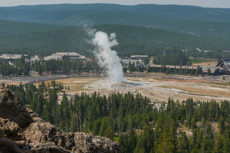 Looking Over Old Faithful and the Crowds Gathered For The Eruption Stock Photo