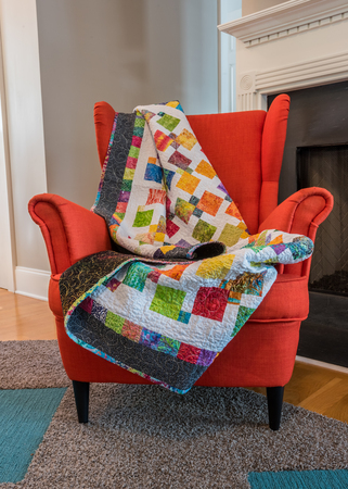 Quilt Draped Over Back of Orange Chair in front of fire place Imagens - 92554184