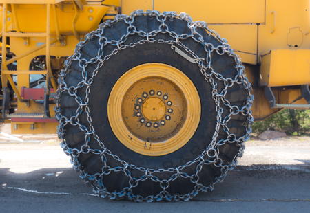 Snow Chains on Industrial Snow Blower Wheel in parking lot Stock Photo