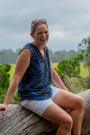Laughing Woman in Outdoor Marsh Area while sitting on large tree Stockfoto