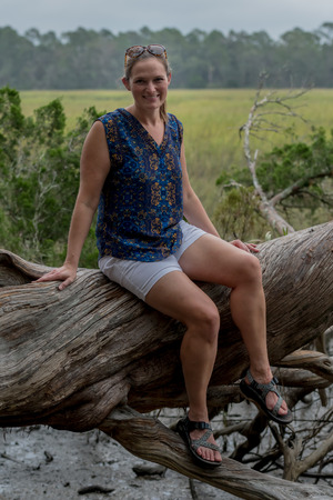 Woman Sits on Large Tree trunk in front of grassy marsh