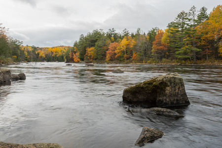The Penobscot River Flows Around Large Boulders with autum colors on trees Stock Photo