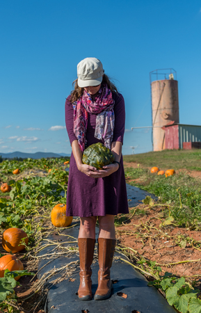 Woman in Pumpkin Patch Holds Heirloom Pumpkin on sunny afternoon