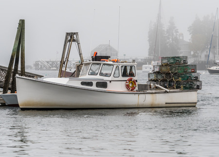 Lobster Traps Stacked on Back of Fishing Boat in overcast marina Stock Photo