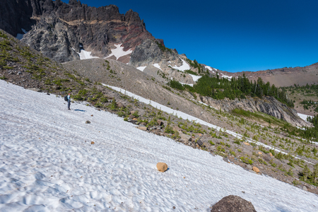 Woman Crosses Snow Field in Oregon Mountains underneath Three Fingered Jack