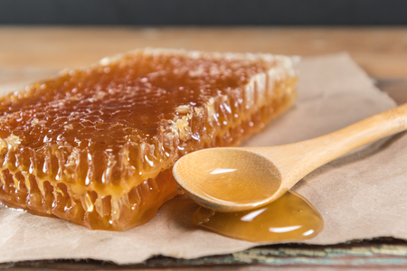 Honey Spills from Wooden Spoon Stock Photo